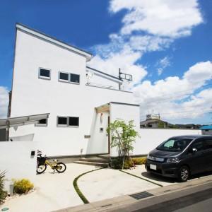 吹抜け空間と無垢材が印象的な白いデザイン住宅